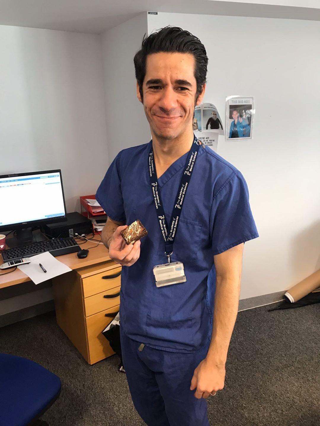A photo of a NHS staff member holding a brownie from Mary's