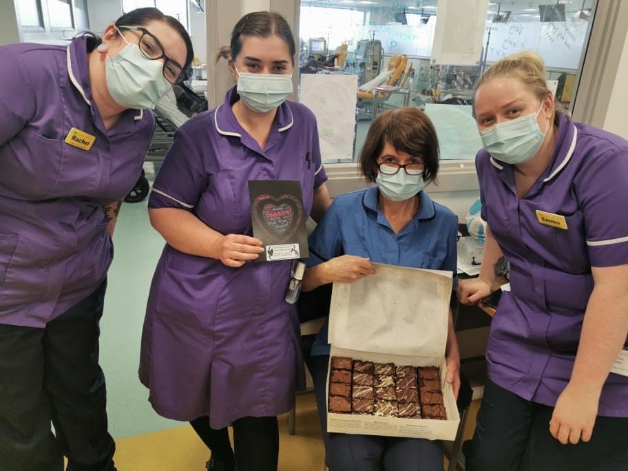 A photo of four NHS staff members, holding a box of Mary's Treats